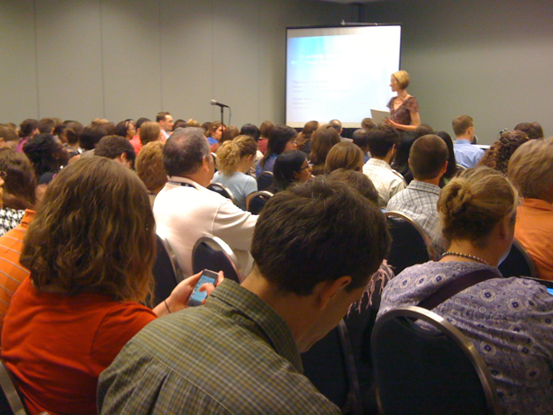crowded room of people watching presentation