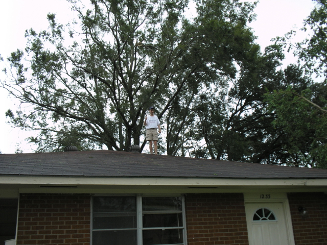 man on roof of house